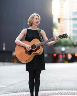 Naomi Ashley with guitar, photo by Paul Goyette